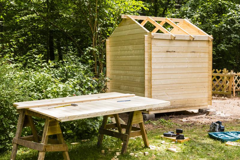 Небольшой деревянный сарай с двускатной крышей на стадии строительства